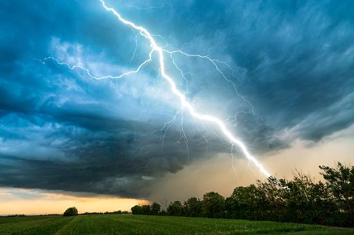 dramatic lightning thundertbolt bolt strike in daylight rural surrounding bad weather dark sky